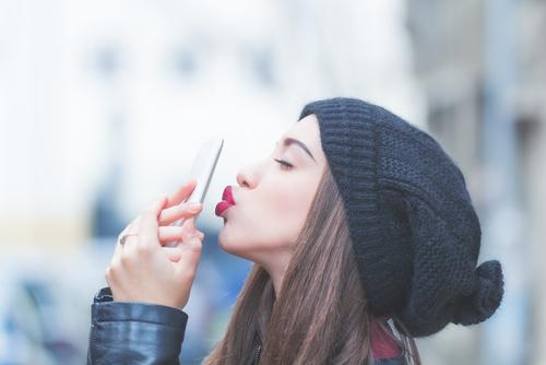ケータイにキスする女性